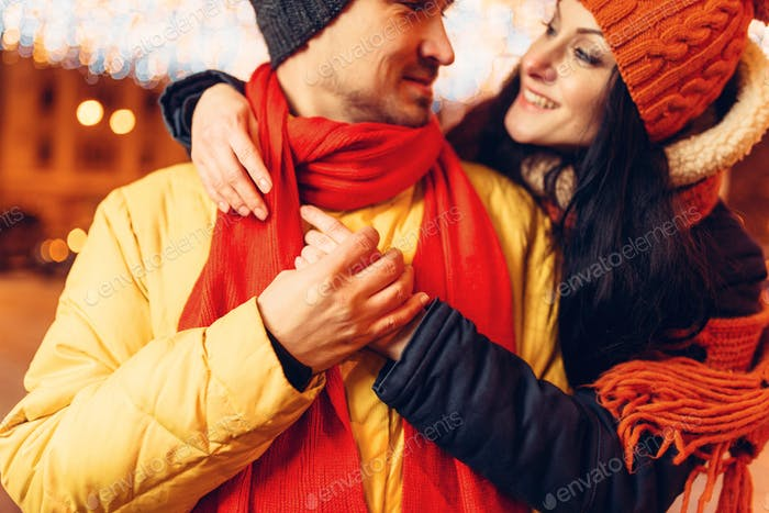 Winter evening, smiling love couple hugs on street