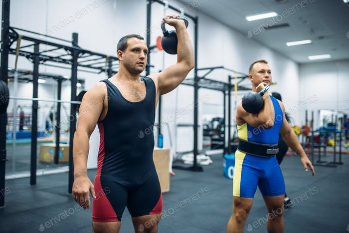 Athletes with weights in gym, kettlebell lifting