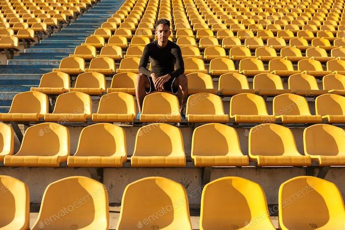 Junger attraktiver Afroamerikaner Sportler, der nach dem Laufen unter leeren Stadionsitzen ruht