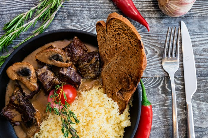 Close view mushroom beef stroganoff in frying pan with couscous