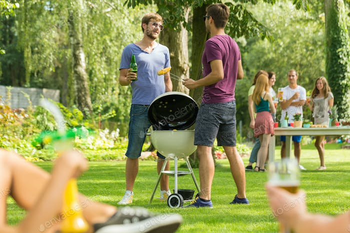 Two men standing beside grill
