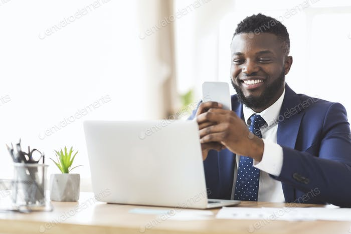 Cheerful businessman chatting with friends on phone, working in office