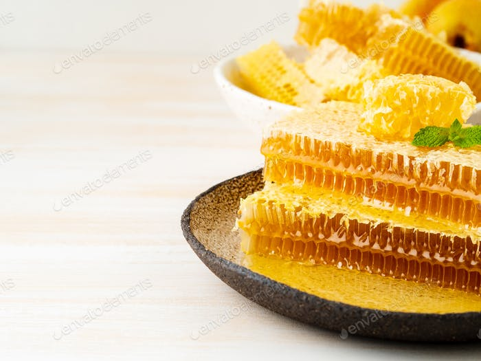 honey in honeycomb, close-up, on brown ceramic plate, on wooden white rustic table, copy space