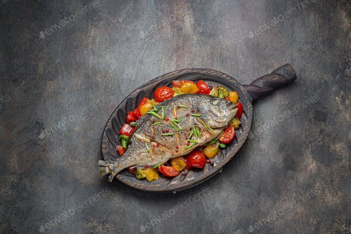 Fried fish with vegetables on cutting board, copy space