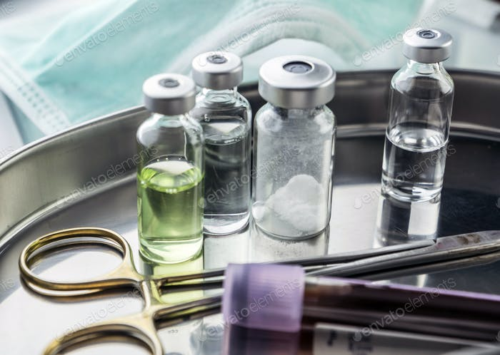 Scissors and vials of blood samples in a tray on a table of a hospital, conceptual image