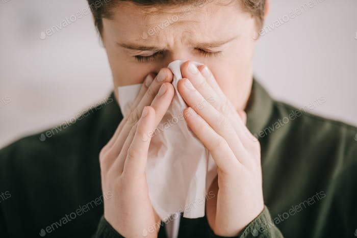 close up of man sneezing in tissue at home