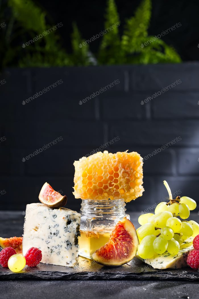 Grape, cheese, figs and honey with a glasses of red on a stone black background