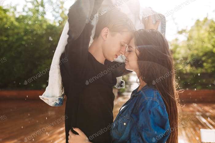 Young happy couple in love covering from the rain with denim jacket standing under rain in park