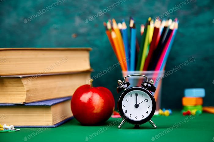 Back to school supplies. Books and red apple