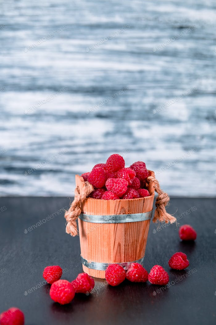 Red raspberries in a basket on black wooden background. Close up. Copy space.