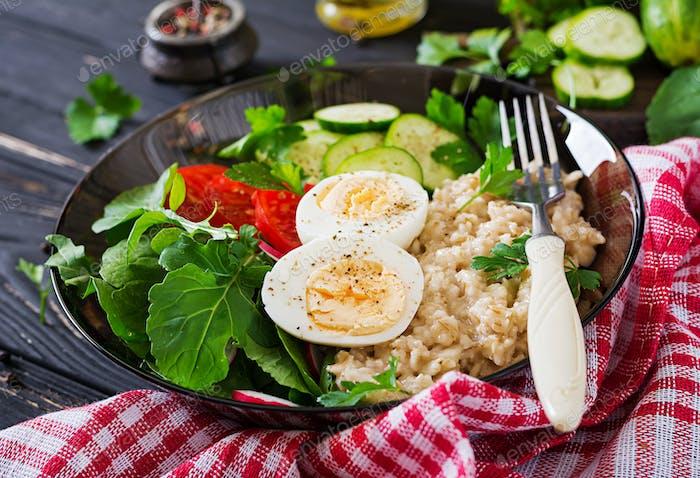 salad of fresh vegetables - tomatoes, cucumber, radish, egg, arugula and oatmeal