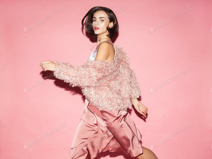 fashionable woman in pink dress on pink background