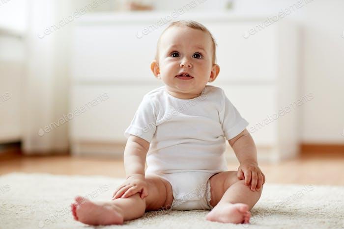 bébé heureux garçon ou fille assis sur le sol à la maison