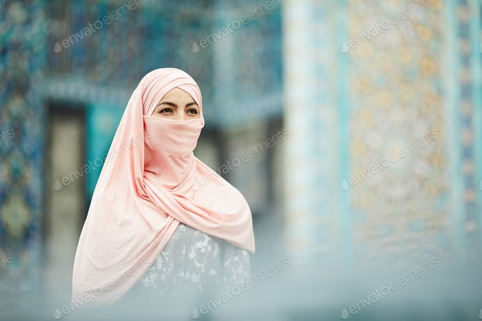 Introspective Muslim woman visiting mosque