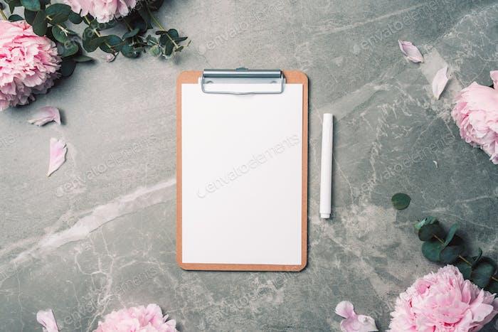 Мода женственная концепция блогера. Женское рабочее пространство с ноутбуком, буфером обмена, бумагой, розовым пионом
