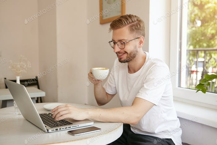Young good looking man with beard is sitting at table in cafe and drinking coffee while typing text