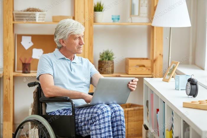 Disabled man with laptop at home