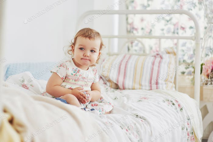 baby girl in cute dress siting at bed playing with toys by the home