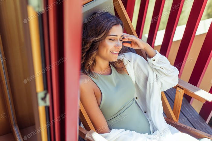 Latin young woman enjoying the sun on the balcony