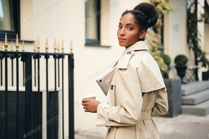 Gorgeous African American girl in stylish trench coat with laptop and coffee looking in camera