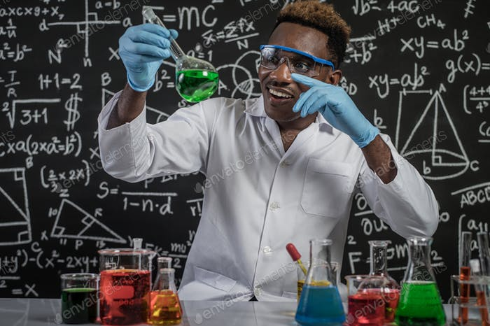 The scientists pointed their hands and looked at the green chemicals in the glass at the laboratory.
