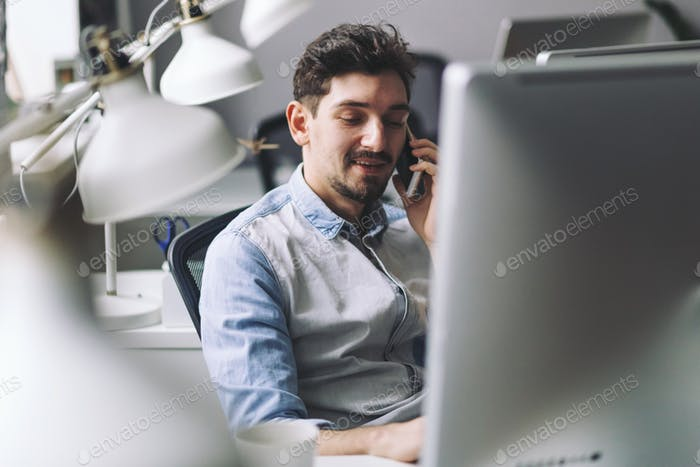 Handsome businessman working in office using mobile phone