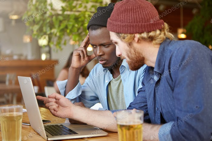 Young men with concentrated looks looking at laptop computer pointing with finger at screen discussi
