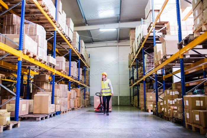 Woman warehouse worker with hand forklift truck.