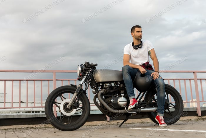 Hombre brutal sentarse en la motocicleta personalizada Cafe Racer.
