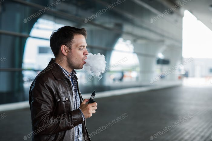 Man with a bristle smoking e-cigarette vaporizer box mode outdoors near the airport terminal before