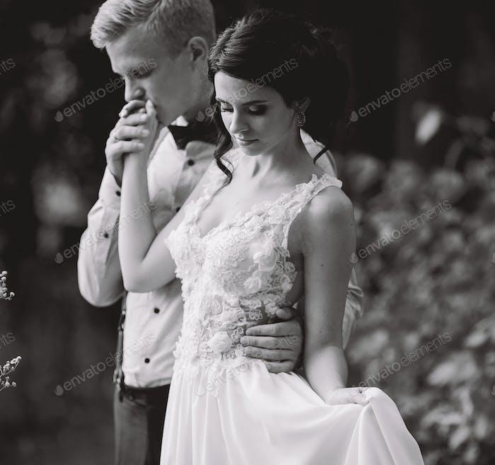 Bräutigam sanft umarmt seine Braut