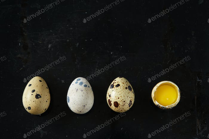A row of some quail eggs on black rusty background