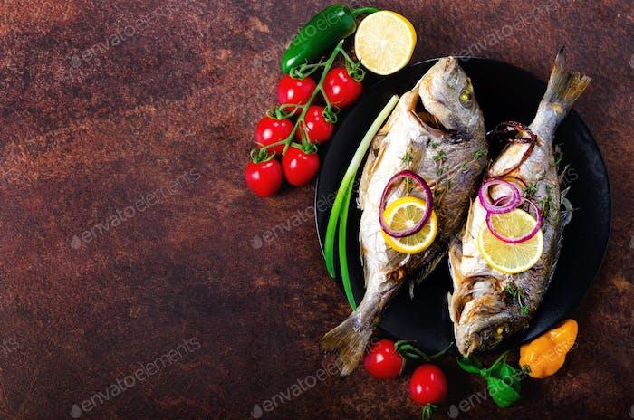 Gekochte gebackenen gegrillten Fisch, Dorado, Seebrassen mit Zitrone, Kräutern, Gemüse und Gewürzen auf rustikalen