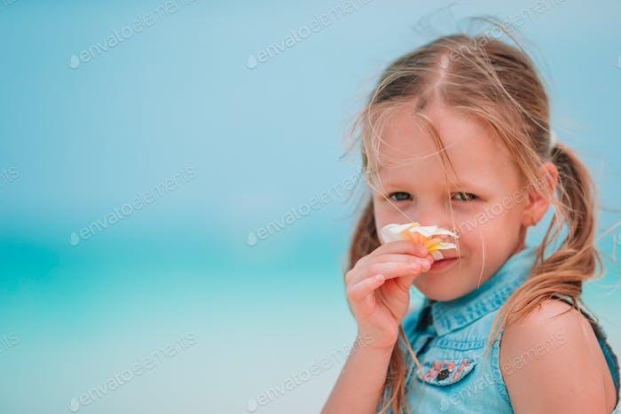 Kleine entzückende Mädchen riecht bunte Blumen am Sommertag