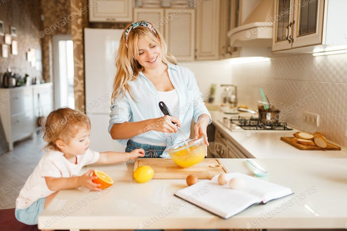 Mother and her daughter mixing fruits in a bowl