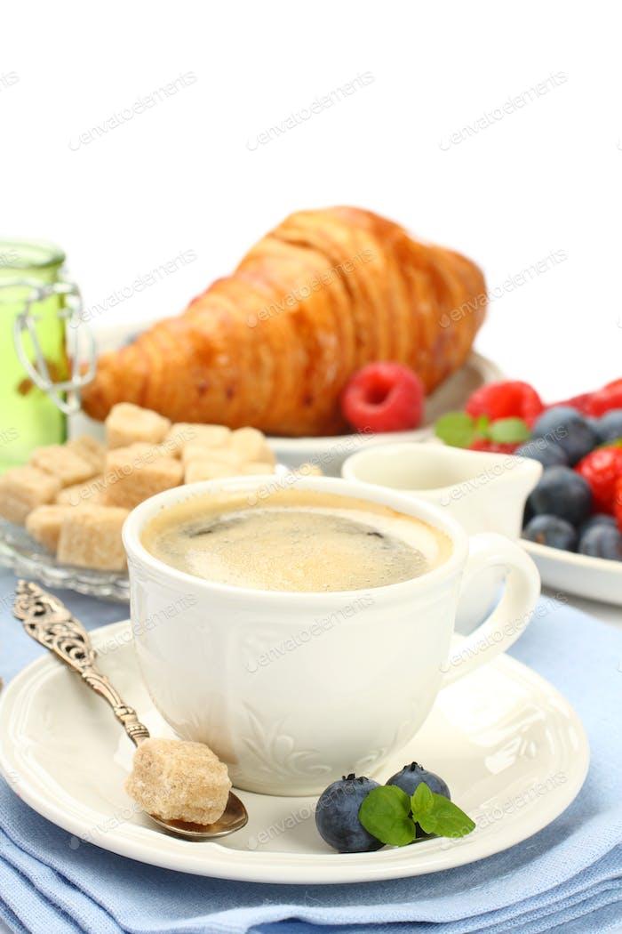 Frühstück mit Tasse Kaffee, Croissants und Beeren
