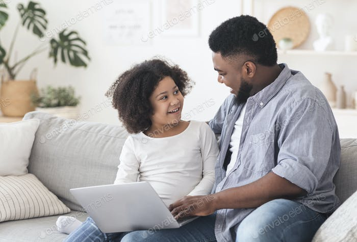 Caring Black Father Teaching Little Daughter How To Use Laptop Computer