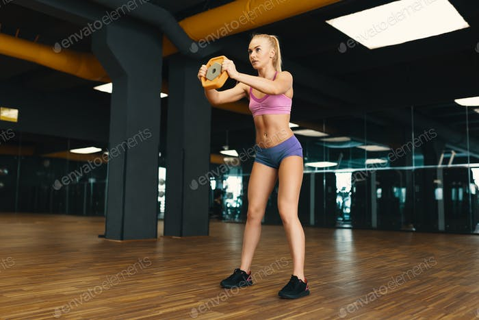 Image of young attractive female in mini shorts doing exercise o
