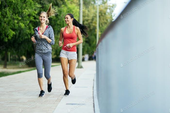 Two sporty women jogging in city