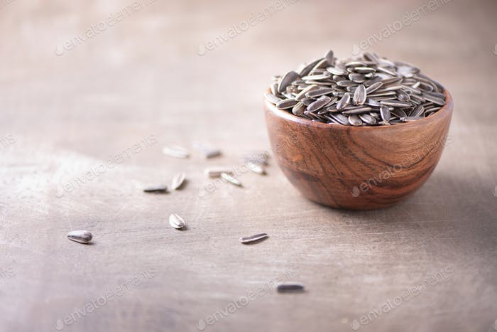 Sunflower seeds in wooden bowl on wood textured background. Copy space. Superfood, vegan, vegetarian