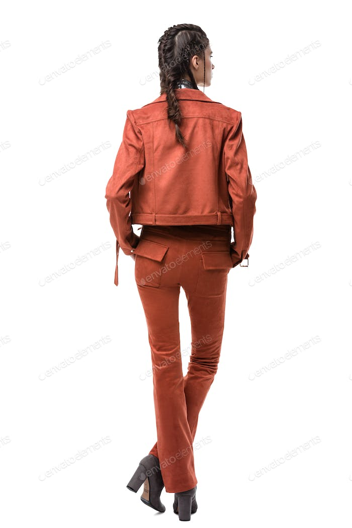 Young pretty lady standing from back in light brown suede jacket and trousers on white background