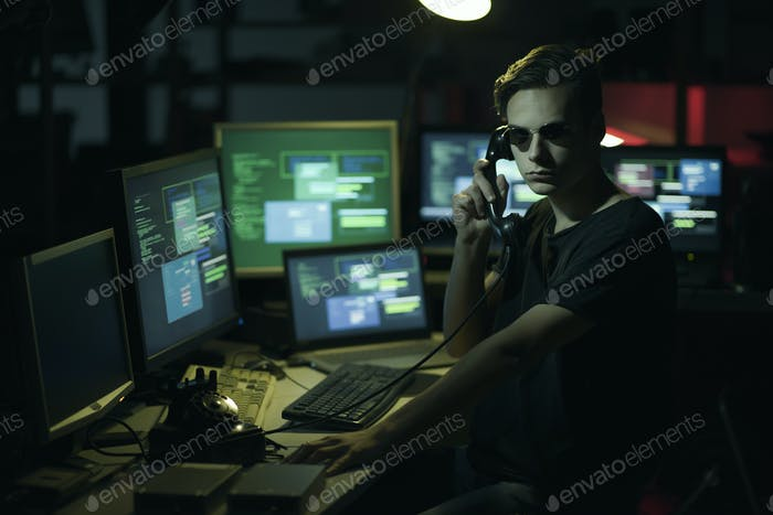 Hacker hoding a receiver and computer screens
