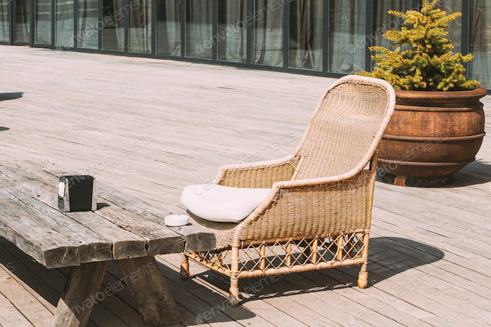 Wicker Furniture On Balcony At Sunny Summer Day. Home Exterior With Chair And Wooden Table In A