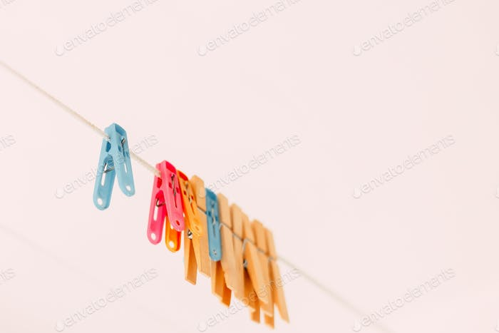 Colored clothespins on a rope on a blurred background