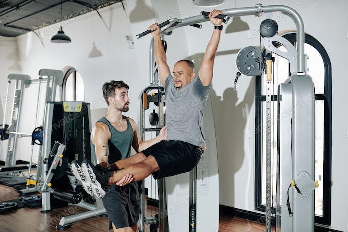 Trainer helping man to strengthen body