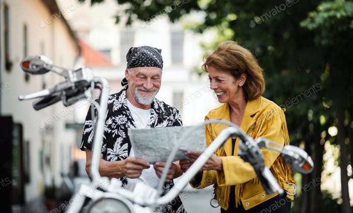 A cheerful senior couple travellers with motorbike in town, looking at map.