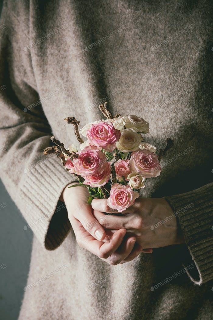 Pink roses in female hands