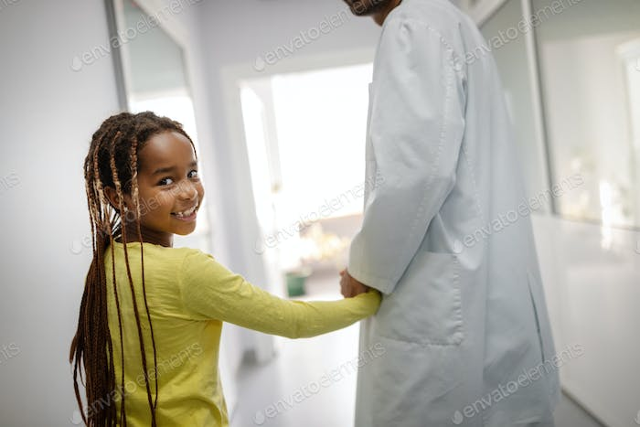 Pediatrician doctor holding young girl kid hand in hospital
