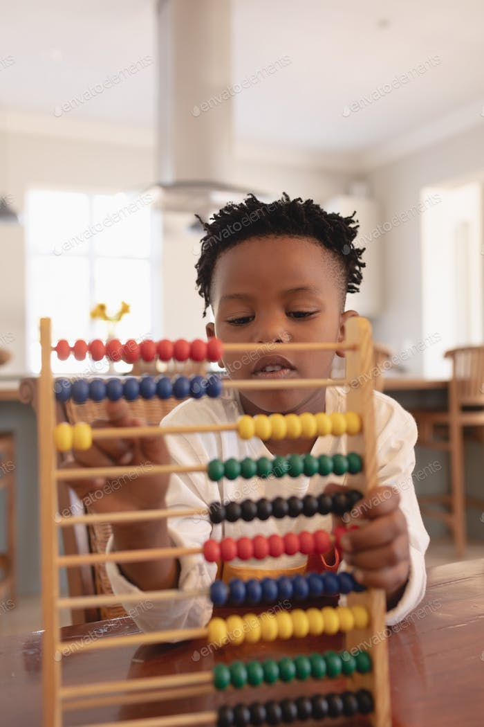 Cute boy learning mathematics with abacus at table