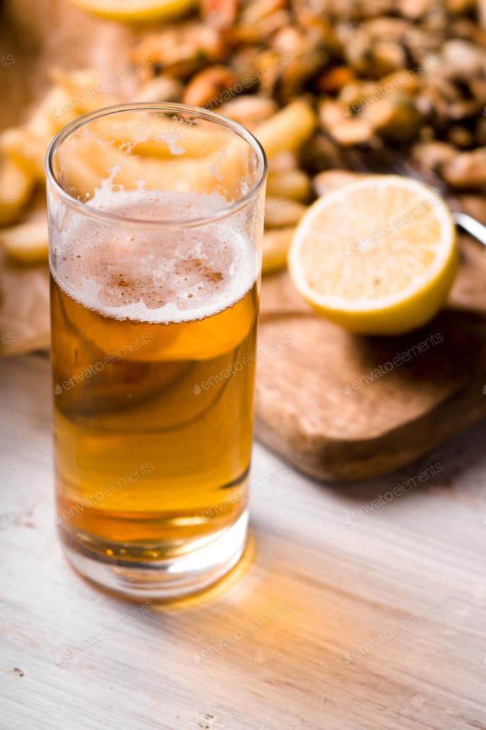 Glass of beer with blurred snack on the white wooden table